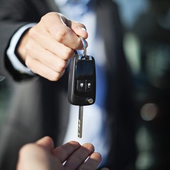 male adult dealer hand giving car keys to female person, close-u